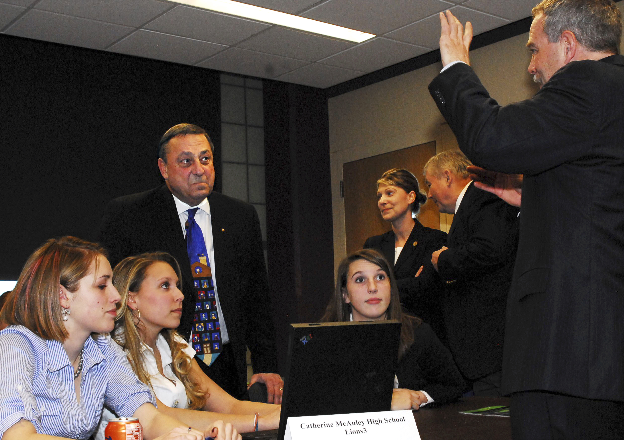 Gov. Paul Lepage and Katherine McCauley High School Students Tabitha Dupuis, Alexa Dumont and Elisabeth Perkins listen as University of Southern Maine Prof. Jeffrey Gramlich talks about the Junior Achievement of Maineâ??s Titan Challenge competition on Thursday.