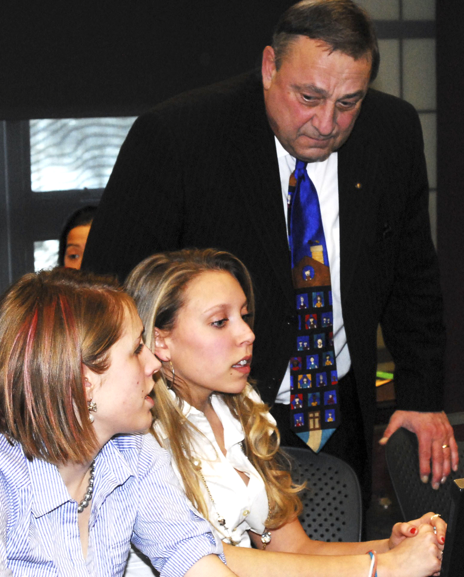 Katherine McCauley students Tabitha Dupuis, left, and Alexa Dumont, right, listen as Gov. Paul LePage gives them some business advice at the Junior Achievement of Maineâ??s Titan Challenge competition at the University of Southern Maine on Thursday.