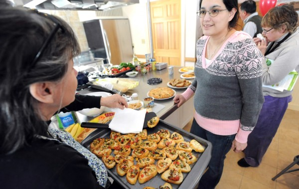 Maria Emerson (left) offers some clams casino bruschetta to to Margaret Nicholas at the Labor of Love Nutrition Center and Food Pantry in Eastport on Friday.