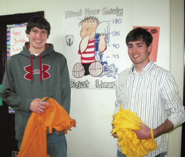 Caribou High School National Honor Society members Cole Sirois and Caleb Chapman stand in front of the Project Linus poster, created by classmate Jenna Selander.