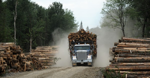 "A Canadian logging truck with a load of wood is bound for Canada from Township 16 Range 14 in Maine in 2009. The Department of Labor canceled public hearings on Dec. 21 in Jackman on allegations that two Canadian firms hired Canadian workers without following the state's laws for use of foreign or ""bonded"" laborers."