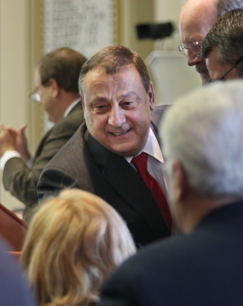 Gov. Paul LePage greets legislators as he prepares to announce his two-year state budget to a joint session of the Maine Legislature on Thursday.