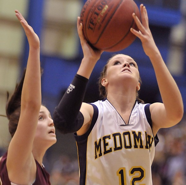 Medomak's Lindsay Ranquist (12) gets a look at the basket past Nokomis' defender Kylie Richards, left, in the first half of their Eastern Maine Class B final game at the Bangor Auditorium Saturday, Feb. 26, 2011.
