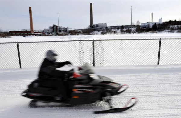 A snowmobiler passes the dormant Millinocket paper mill early Wednesday afternoon. Meriturn Partners, a San Francisco investment group, recently signed a tentative agreement to buy the Millinocket and East Millinocket paper mills. Principals of the group met with mill, union and town officials Wednesday.