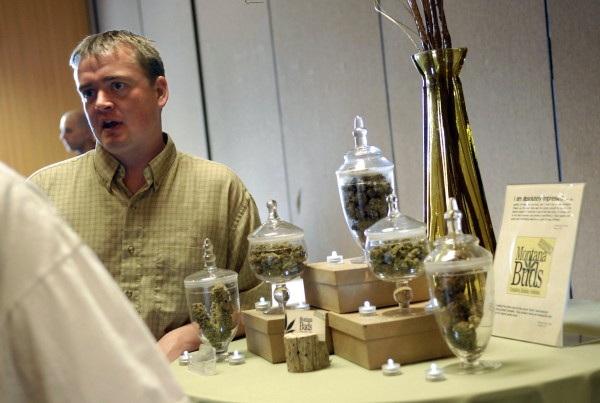 In this May 18, 2010 photo, Chuck Campbell, with Montana Buds, talks with a new card holder about the services he offers, as part of a so-called cannabis caravan in Helena, Mont. The Montana Legislature is considering a bill to repeal the state's medical marijuana law, which is expected to easily pass the House.