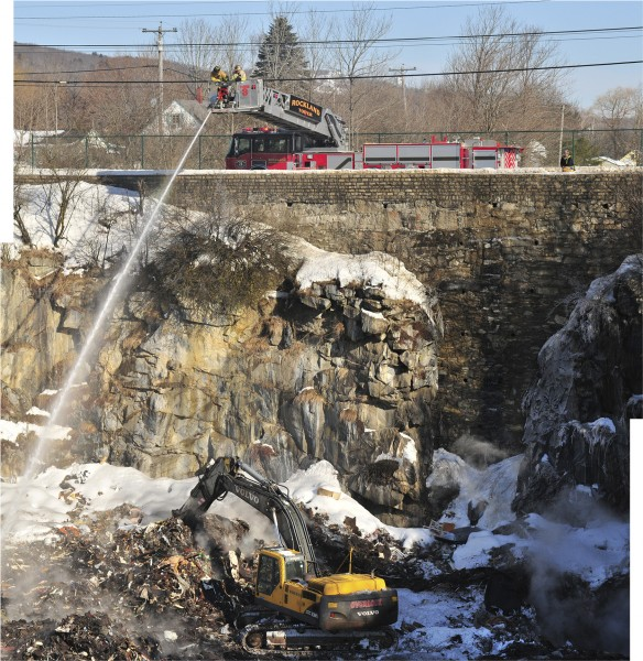 Rockland firefighters hose down smoldering debris while an excavator claws at the contents of the city landfill on Saturday.