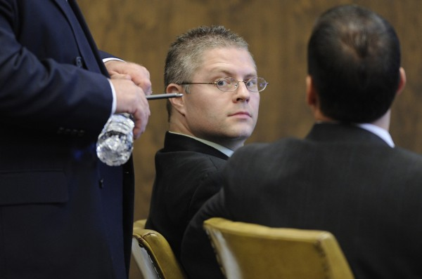 During a recess at Penobscot Superior Court, Ryan Witmer of Eddington briefly turns toward the gallery behind him while conferring with his defense team — Portland attorneys Daniel Lilley (left, standing) and Darrick Banda (seated, right) on Oct. 26, 2009. Lilley and Banda were not representing Witmer at the time of the thefts.