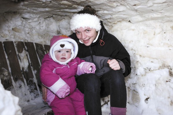 Angela Bertholdt and her daughter Ariah take a seat inside their snow fort built by Bertholdt and her boyfriend, Tyler Schools, in Littleton recently.