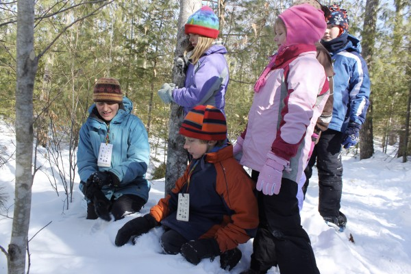 Tanglewood Camp environmental educator Leah Trommer talks about ermine tracks to campers Joseph Potter, 8, of Belfast (from left), Sydney Densmore, 9, of Waldo, Emily Izajs, 8, of Islesboro and Jaydon Schumacher, 10, of Hope, on Wednesday at Tanglewood Camp in Lincolnville at the two-day Winter Survivors camp during school vacation