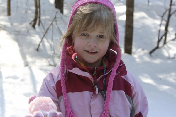 Emily Izaijs, 8, of Islesboro holds up a snowball she has made while playing a tracking game in the forest on Wednesday at Tanglewood Camp in Lincolnville at the two-day Winter Survivors camp during school vacation.
