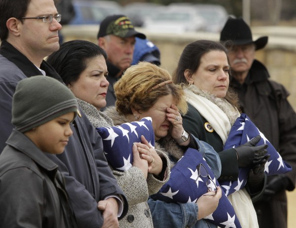 Elizabeth Marchan, daughter of the late U.S. Air Force Col. James E. Dennany of Kalamazoo, Mich., wipes away tears as she stands by her siblings, James Dennany, from upper left, Marie Lara and Melissa Harrington, right, during a burial ceremony for their father and Maj. Robert L. Tucci of Detroit at Dallas Fort Worth National Cemetery, Friday, Jan. 14, 2011, in Dallas.