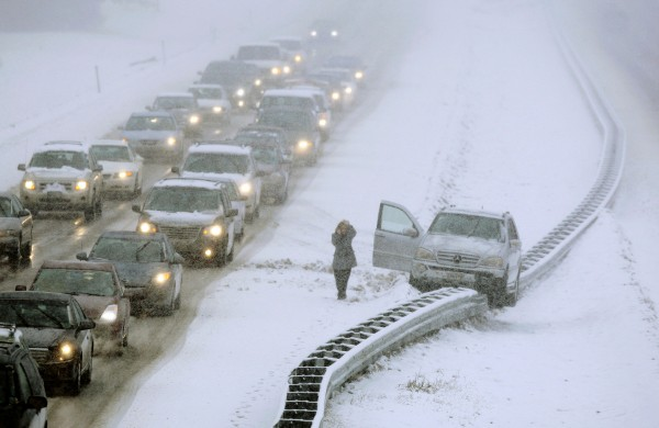 A woman calls for help on a cell phone after climbing out of a vehicle that ended up on a guardrail in the median of Interstate 295 during a snow storm in Cumberland, Maine, Friday, Feb. 25, 2011.