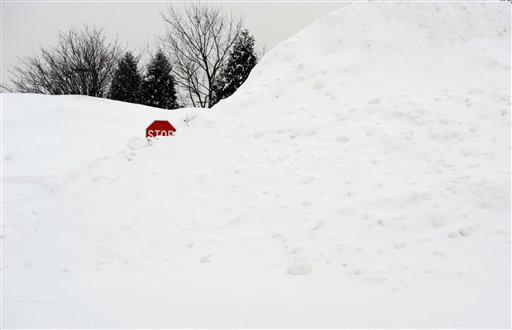 A stop sign pokes out of a large pile of snow at the end of a street in Enfield, Conn., Tuesday, Feb. 1, 2011.