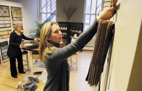 Heather Bass, right, hangs upholstery samples as her mother, Janet St. John, left, helps her in one of the rooms at 15 State Street that make up Bangor's newest retailer, The Blue Heron.
