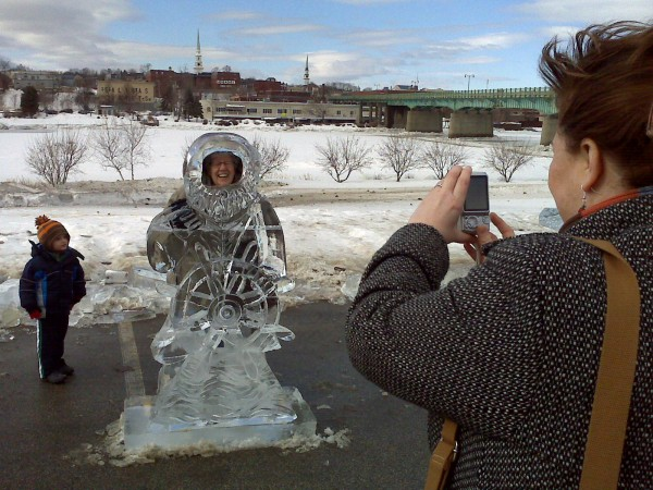 Michelle Libby of Bangor takes a picture of her mom, Sandy Rock, and Devin Rock, both of Etna, by an ice sculpture at Brewer Winterfest on Saturday. The sea captain ice sculpture was one of three ice creations created by Jeff Day of New Hampshire.