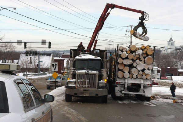 Workers clean up logs that fell from a logging truck onto North Main Street in Brewer  around 8:30 a.m. Monday, February 7, 2011.