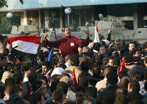 Egyptian anti-government protesters shout in front of the Egyptian television headquarters in Cairo, Egypt, Friday, Feb. 11, 2011.