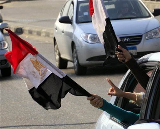 Anti-government protesters peer out of their vehicle as they flash V signs and wave by Egyptian flags in Cairo street, Egypt, Friday, Feb. 11, 2011.