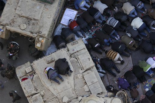 Anti-government protesters pray atop an Egyptian APC vehicle during traditional Muslim Friday prayers in Tahrir Square in downtown Cairo, Egypt, Friday, Feb. 11, 2011.