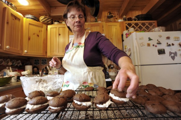 Pat Huckins arranges freshly baked whoopie pies on a cooling rack at her home in Greenville on Thursday afternoon. Huckins and others are preparing their chocolate treats for Sunday's Moosehead Chamber of Commerce Chocolate Festival in Greenville.