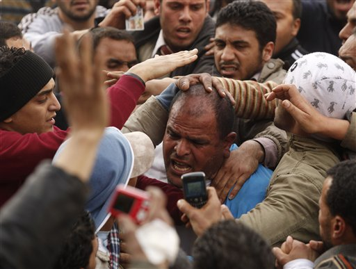 Anti-government demonstrators grab a man they suspect to be a supporter of Egyptian President Hosni Mubarak in Cairo's Tahrir Square, Egypt, Thursday, Feb. 3, 2011. The Egyptian military is taking up positions between anti-government demonstrators and supporters of President Hosni Mubarak. Hours after automatic gunfire hit the protest camp at Tahrir Square,  soldiers carrying rifles could be seen lining up between the two sides late Thursday morning. Several hundred other soldiers were moving toward the front line.