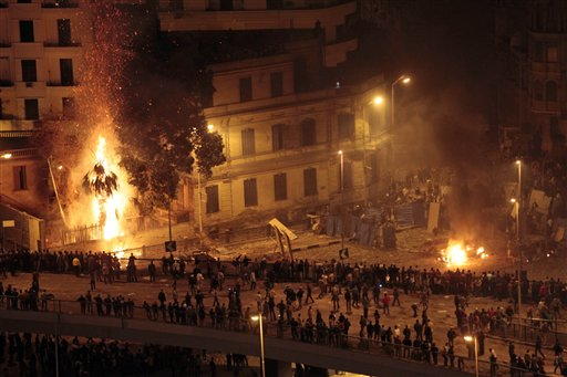 Pro-government demonstrators, bottom, clash with anti-government demonstrators, top right, as a palm tree burns from a firebomb, in Tahrir Square, the center of anti-government demonstrations, in Cairo, Egypt, early Thursday, Feb. 3, 2011. Thousands of supporters and opponents of Egyptian President Hosni Mubarak battled in Cairo's main square all day Wednesday, raining stones, bottles and firebombs on each other in scenes of uncontrolled violence as soldiers stood by without intervening.