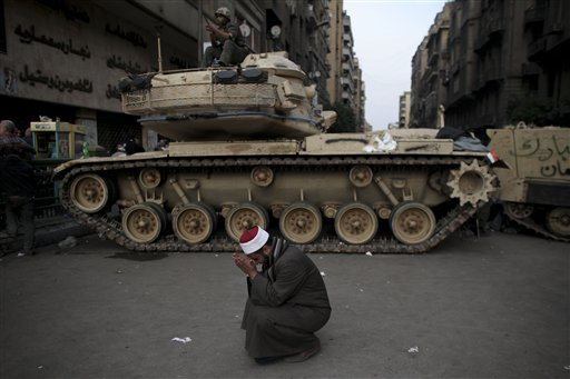 An Egyptian Muslim cleric cries in front of on army tank in Tahrir, or Liberation square, in Cairo, Egypt, Wednesday, Feb. 2, 2011.