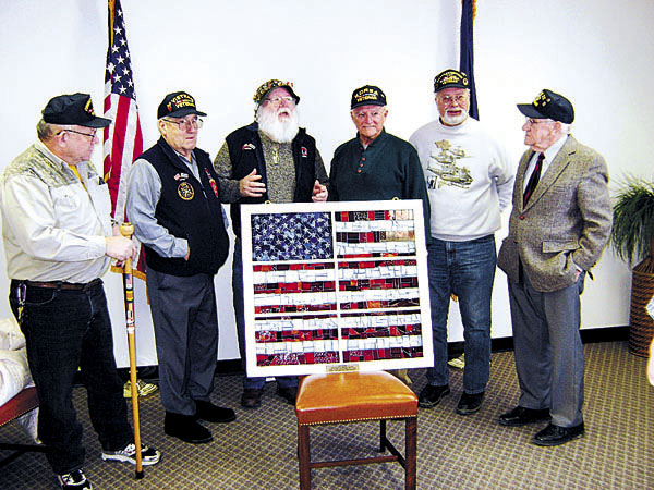Volunteers in the Ambassadors of Freedom Program at Cole Land Transportation Museum on Jan. 28 in Bangor — Carl Carlstad (from left), John Moore, Ed Parent, Al Gibson, Gordon Warner and Ray Parsons — display the stained-glass window of a United States flag made by students from Oxford Hills Middle School, which sends the largest class to the museum each year. Not pictured is Chuck McClead.