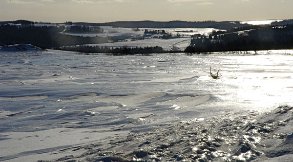 The combination of extreme cold and strong winds create glistening ice-covered fields in northern Maine Saturday.