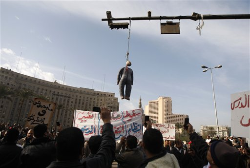 An effigy depicting President Hosni Mubarak hangs while perople demonstrate in Tahrir, or Liberation, Square in Cairo, Egypt, Tuesday, Feb. 1, 2011. Security officials say authorities have shut down all roads and public transportation to Cairo, where people are converging to demand the ouster of Egyptian President Hosni Mubarak after nearly 30 years in power.