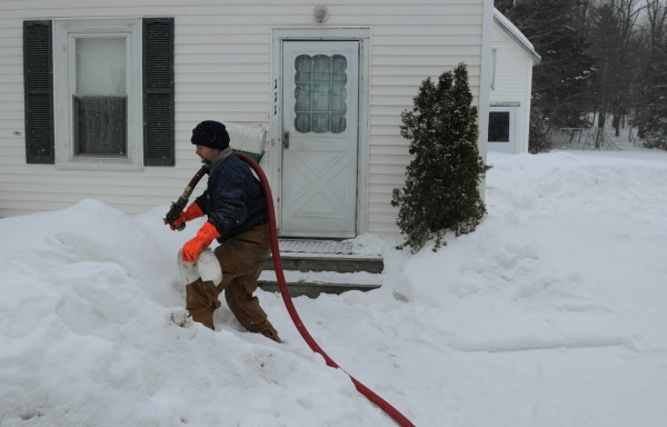 Curtis Emerson prepares to pump 40 gallons of oil into the house of a family on heat assistance on Oak Street in Ellsworth on Tuesday. Money provided by the state to assist low-income Mainers who need help heating their homes is critically low.