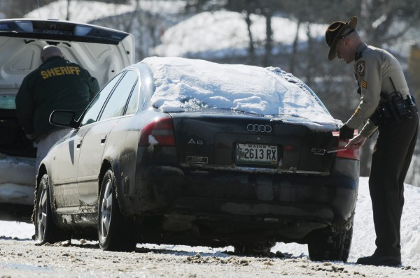 Penobscot County Sheriff's detectives and officers seal a Black Audi A6 along the side of Rt. 2 in Milford on Thursday. The driver was arrested in conncetion with a earlier robbery of the Milford Mobil on the Run.