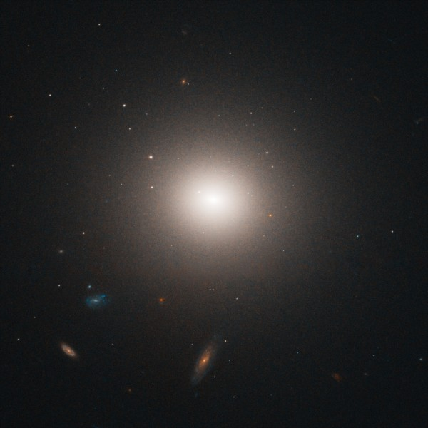 NGC 4458, a galaxy in the Virgo cluster of galaxies. The smaller swatches of light are also galaxies.