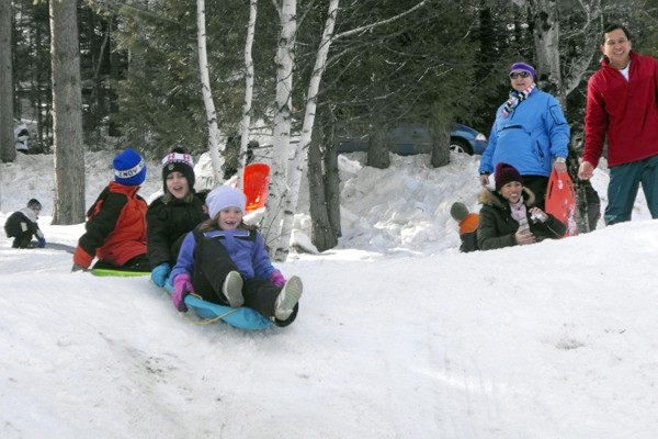 Children and adults enjoyed the sliding hill at Aroostook State Park during the third annual Take It Outside Winter Family Fun Day in February 2010. Participants brought their own sleds or toboggans for a fast 200-yard run down the hill out onto Echo Lake. Hundreds of people came to the Presque Isle park to ski, showshoe, ice skate, take dog sled rides and more.
