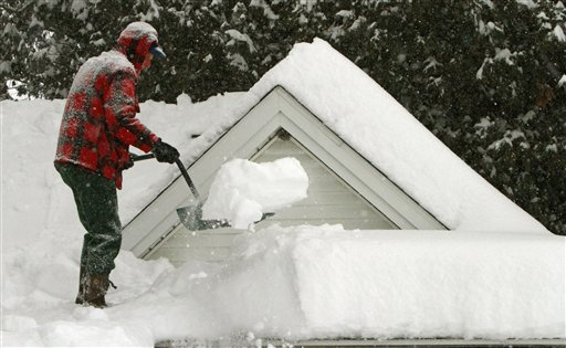 Harry Eastman shovels the snow off his garage roof in Barre, Vt.  Doctors across the battered Northeast are seeing a spike in strained muscles from shoveling snow, broken bones from slick stairs and sidewalks, and dangerously low blood banks as fewer people venture out.