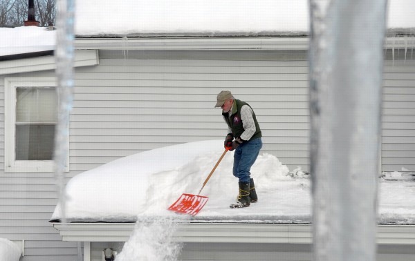 Don Hoxie of Old Town shovels snow off of the roof of his Center Street home on Saturday. Hoxie said that there was about five feet on snow piled on the roof. &quotIt's been entertaining,&quot Hoxie said of the abudance of snow this winter.