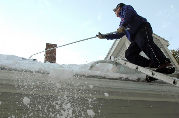 Tom Robertson removes a blanket of snow from the roof of a client's home in Hampden on Monday. Robertson estimated that two to three tons of wet, heavy snow had accumulated on the roof and that it would take him and his crew of three workers about five hours to clear.