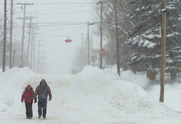 Paula Alexander, left, and Jason Petrenick, right, both of Bangor, walk through the snow on Garland Street on Wednesday morning. The two were walking three blocks for an appointment. &quotIt's safer to walk than to drive,&quot said Alexander of the road conditions.