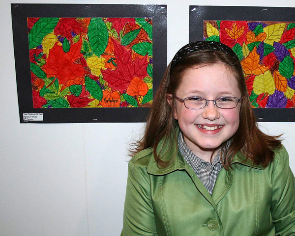 Katelyn White, a fifth-grader at Easton Elementary School, poses next to one of the two art pieces she has on display at the Essence of the North student art exhibition at the Aroostook Centre Mall. White said she likes this one, ââ?¬Å?The Colors of Fall,ââ?¬Â because ââ?¬Å?I love pictures of leaves and fall, and I love coloring leaves because they're so colorful.
