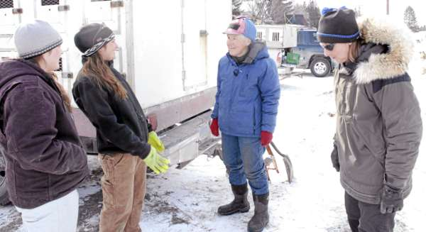 Sisters Holly Dionne and Amy Dionne (left and second from left) get a few  pointers from mushing veterans Jamie Nelson (center) and Ann Stead Friday  afternoon at the Can Am Crown registration and vet check in Fort Kent.