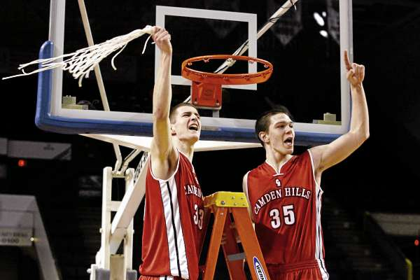 Camden Hills Regional High School's Keegan Pieri (33) and Tyler McFarland (35) celebrate their victory Friday, March 4, 2011 following the Class B state basketball finals against Cape Elizabeth High School at the Cumberland County Civic Center in Portland, Maine.