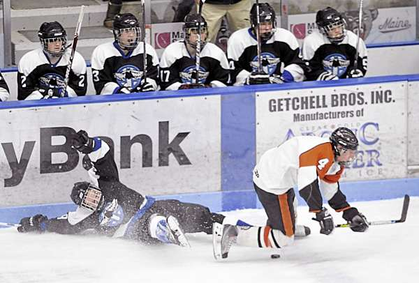 Houlton-Hodgdon's Parker Sanderson (left) trips up Brewer's Evan Nadeau in first-period action during the Easterxn Maine Class B final Tuesday night at Alfond Arena in Orono. Brewer defeated Houlton-Hodgdon 10-0.