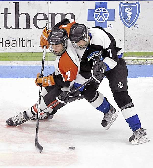 Jake Valley (left) of Brewer and Ian Gervais of Houlton-Hodgdon try to push each other away from the loose puck in the first period of Tuesday night's Eastern Maine Class B hockey semifinal at Alfond Arena in Orono. Valley scored once for the Witches, who rolled to a 10-0 win over the Black Hawks.