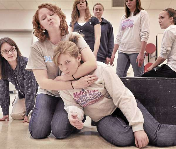Central High School student Dani Cookson (kneeling, front) tells her two cats Kortlyn Gilley (left) and Katrina Lessard (front) how much she loves them even with the cat hair.