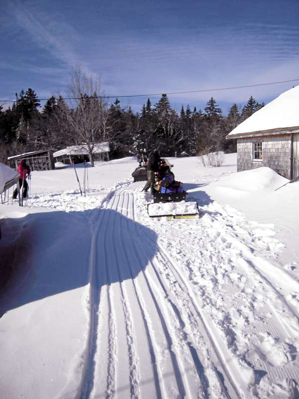 Luggage is towed from camp to camp on sleds pulled by snowmobiles that set track as they traversed the trails.