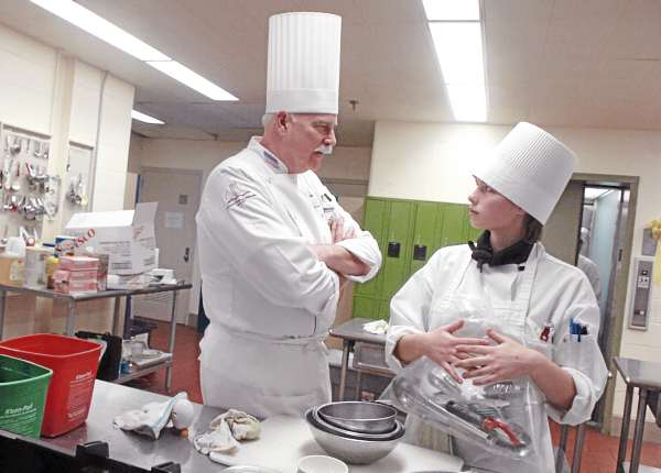 Professional chef Gary Sheldon of the Academy of Chefs talks with Brooklyn Pinkham of Augusta at the conclusion of the culinary arts competition at the SkillsUSA Maine Championships held on Friday, March 11, 2011, at United Technologies Center in Bangor. The annual event is a state-level competition for high school and college students enrolled in trade, technical, and skilled service instructional programs.