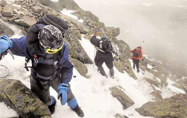 Bob Bukaty (left), Cory Ricker, (center) and Roy Curtis head down the Abol Slide Trail on Mount Katahdin after making the decision to turn back a few hundred feet before reaching the Tableland. The wind gusts kept knocking us off ballance and the semi-truck-like sound indicated higher winds on the plato.  The members of the group estimated the wind gusts were about 60 miles an hour during the climb in Baxter State Park Friday March 18.