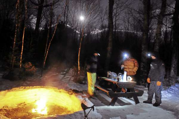 The group stands around the fire after a good jambolaya dinner at Abol Campground in Baxter State Park Friday March 18.  The failed attempt to climb Mount Katahdin did not bring down our spirits. We agreed it was for the better not to risk injury in the high winds. Pictured are from left: Cory Ricker, Roy Curtis and Bob Bukaty.
