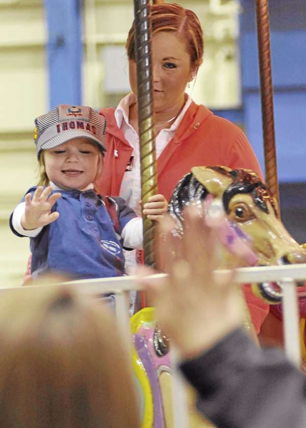 As they ride the Ferris wheel,  Abby Randall of Old Town and her son Christian James, 2, spot Christian's maternal grandmother Karen Randall waving to them  from the sideline during their visit to the Bangor YMCA Spring Fair at the Bangor Auditorium Friday.