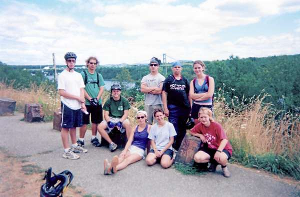 Nine cyclists pose at the US Route 1 south turnout in Prospect, Maine, with the old and now-closed Waldo-Hancock Bridge spanning the Penobscot River. Bucksport is in the background.